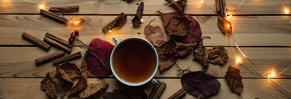 Fall blog post ideas - autumn leaves on table with hot cup of chai, cinnamon sticks and fairy lights
