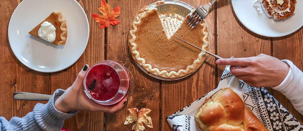 Wooden table with apple pie, autumn leaves and festive drink